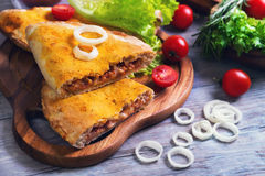 Closed pizza calzone on a light wooden background Royalty Free Stock Photography