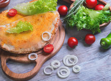 Closed pizza calzone on a light wooden background Stock Image