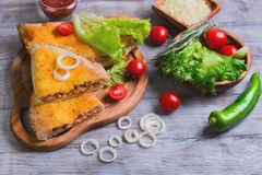 Closed pizza calzone on a light wooden background Royalty Free Stock Image