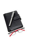 Closed Planner with Glasses and Pen. Closed Black Planner, with a silver pen on top, and a glasses on bottom. On white Stock Photos