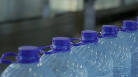 Closed plastic bottles with transparent water move along conveyor. stock video