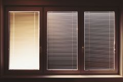 Closed plastic window on sunny day with horizontal plastic blinds stock photography