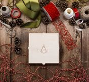 Closed plywood box with xmas tree on the cover on a wooden table surrounded by ribbons, cord, ropes. And pine cones. Preparing for the new year royalty free stock images