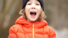 Closed portrait of a European boy in a winter hat. He`s serious, and then he starts screaming stock video
