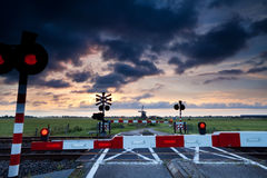 Closed rail crossing at sunrise and windmill Stock Image