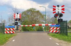 Closed railroad barriers at a rural railway crossing in the polder, Netherlands Stock Images