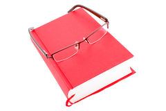 Closed red book isolated on a white background. With glasses Royalty Free Stock Images