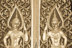 Closed red Buddhism temple gate with golden sculpture creation. Public domain in Bangkok, Thailand black and white stock photos