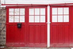 Closed red doors with creeping vines Stock Photo