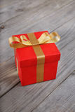 Closed red gift box with gold ribbon Stock Photos