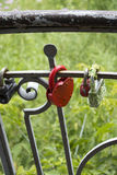 Closed red old lock hanging on the fence. Close-up Stock Photo