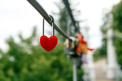 The closed red padlock in the form of heart. On the bridge Stock Images