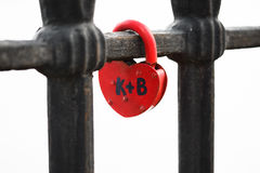 Closed red padlock in the form of heart locked on bridge. Stock Images