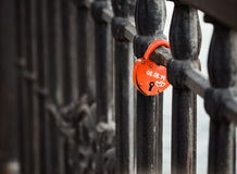 Closed red padlock in the form of heart locked on bridge. Stock Image