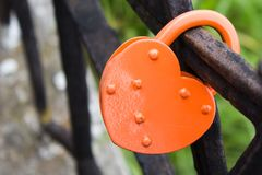 Closed red padlock on iron fence of bridge.  Lock as heart. Symb. Ol of love and marriage Royalty Free Stock Photo