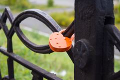 Closed red padlock on iron fence of bridge.  Lock as heart. Symb. Ol of love and marriage Royalty Free Stock Photos