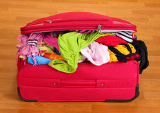 Сlosed red suitcase with clothing Stock Photo