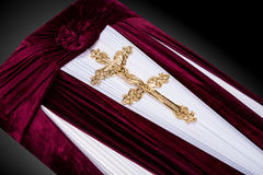 Closed red velvet coffin covered with cloth isolated on gray background. coffin close-up with gold Church cross. Royalty Free Stock Images