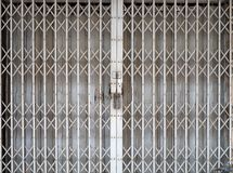 Closed retractable folding metallic gate. In front of traditional shop Stock Photos