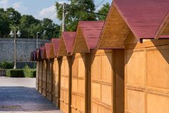 Closed retro stalls shops in park. Closed retro stalls shops. Big models of wooden houses with red roof on sunny summer day. Close up, selective focus Royalty Free Stock Photo