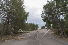 Closed road. Asphalt road cut through a metal fence Stock Photography