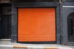 Closed shop exterior covered with orange metal door Stock Image