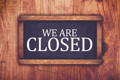 We are closed shop message board. Retro toned chalkboard rustic oak wood store door Royalty Free Stock Photography