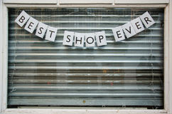 Closed shop window with sign saying. Best shop ever and shutters down Stock Images
