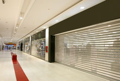 Closed shops in modern mall. Shutters on closed shop units in modern mall Stock Photo