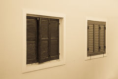 Closed shutters on the light wall. Toned Stock Image
