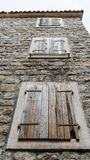 Closed shutters of windows on an old stone wall. Bottom view. Old Rustic facade wall with closed wooden windows. Streets of Kotor stock photo