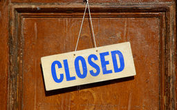 Closed sign. On wood hanging on old historic door of shop Stock Photos