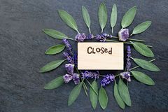 Closed sign for alternative therapy business - word burnt in wood with purple lavender flowers, gren sage herb leaves and amethyst. Clusters on gray / grey royalty free stock photography