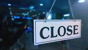 Closed sign board hanging outside store. In dark blue background Stock Image
