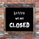 Closed sign on chalk board over brick wall background. Closed sign on vintage chalk board over brick wall background Royalty Free Stock Photos