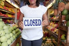 The store is closed. Closed sign in hands of female organic grocery store owner stock image