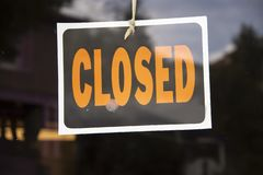 Closed sign hanging in business window by a string - crooked with glob of glue also attaching it to window - some abstract reflect stock images