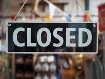 Closed sign on a shop window. Closed sign in a shop showroom with reflections Stock Image
