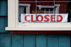 Closed sign in window of green painted wooden building Royalty Free Stock Photography