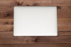 Closed silver laptop on brown wooden table Royalty Free Stock Photo