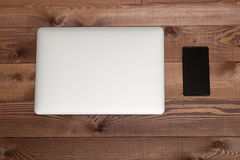 Closed silver laptop  and smartphone on brown wooden table. Closed silver laptop  and black smartphone on brown wooden table Stock Photo