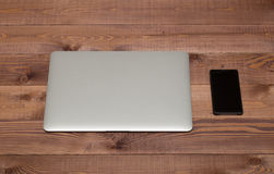 Closed silver laptop  and smartphone on brown wooden table. Closed silver laptop  and black smartphone on brown wooden table Royalty Free Stock Photos