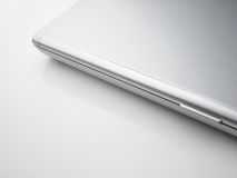 Closed silver laptop on white table Royalty Free Stock Image