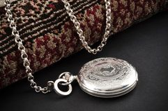 Closed silver pocket watch. Elegant carved silver closed pocket watch with chain over a carpet Royalty Free Stock Photography