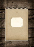 Closed spiral Note book on a dark wood table Royalty Free Stock Photos