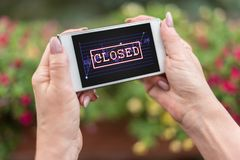 Closed stock market concept on a smartphone. Female hands holding a smartphone with closed stock market concept Stock Images