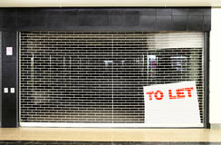 Closed store business space with to let sign. Security shutter down on closed down vacant store business space with to let sign Royalty Free Stock Image