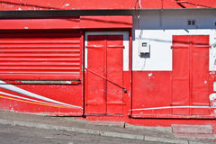 Closed store. Colorful red door and shutter on a closed store Stock Photos