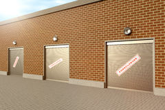 Closed Store. Closed roller doors at business with foreclosure sign Stock Image