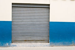 Closed storefront in downtown. Closed after-hours store front in Latin-Americian downtown, blue and white wall roller steal shutters stock images
